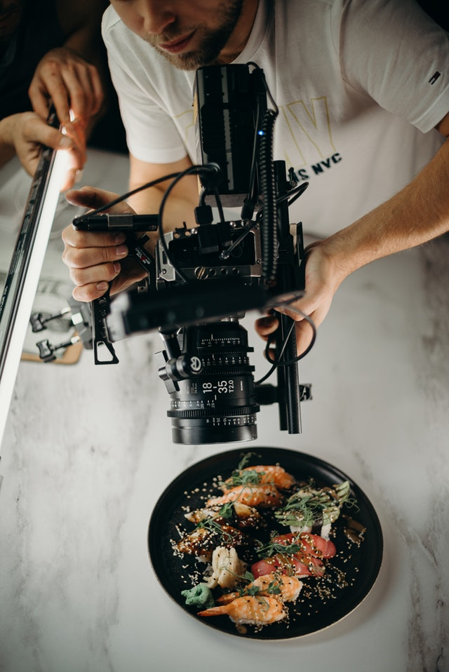 man-using-video-camera-pointing-on-food-on-plate-3298603